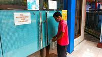 Seorang pria menggembok pintu masuk kantor Camat Bukitraya karena tiga pegawainya positif Covid-19. (Liputan6.com/M Syukur)
