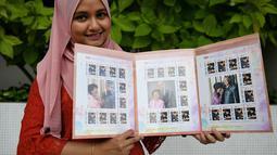 Pekerja pos Nurshafiqa Kasim berpose dengan prangko bergambar PM Malaysia Mahathir Mohamad di sebuah kantor pos di Kuala Lumpur, Selasa (10/7). Prangko bergambar Mahathir ini dijual dalam edisi terbatas. (Mohd RASFAN/AFP)