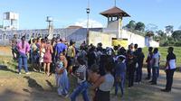 Para warga dan keluarga menunggu dengan khawatir di luar penjara ketika terjadi perang antar geng yang menewaskan 57 orang (AP/Wilson Soares)