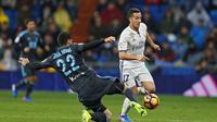 Aksi pemain Real Madrid, Lucas Vazquez (kanan) saat mencoba melewati hadangan pemain Real Sociedad, Raul Navas pada laga La Lga Spanyol di Santiago Bernabeu stadium, Madrid (29/1/2017). Madrid menang 3-0. (AP/Francisco Seco)