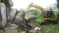 Petugas Satpol PP Kota Bandung menurunkan alat berat untuk meratakan bangunan di atas lahan yang akan dijadikan proyek rumah deret. (Liputan6.com/Huyogo Simbolon)