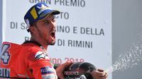 Pembalap Ducati, Andrea Dovizioso merayakan kemenangan dengan menyemprotkan sampanye usai memenangkan balapan MotoGP San Marino di Sirkuit Marco Simoncelli, Misano (9/9). Dovizioso mencetak waktu42 menit 5,426 detik. (AFP FOTO / Tiziana Fabi)
