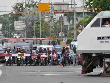 Sejumlah kendaraan menunggu kereta commuterline di perlintasan sebidang Stasiun Pasar Seen, Jakarta, (13/9). Ditjen Perkeretaapian Kemenhub akan menutup perlintasan sebidang di Jalan Letjen Soeprapto, Jakarta Pusat. (Liputan6.com/Gempur M Surya)