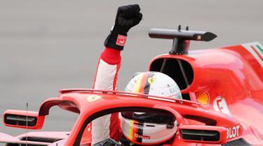 Pembalap Ferrari, Sebastian Vettel mengangkat tangannya saat merayakan kemenangannya di Formula1 Grand Prix (GP) di Montreal, Kanada, Minggu (10/6). Vettel sukses meraih podium juara. (Tom Boland/The Canadian Press via AP)