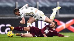 Bek Juventus, Matthijs de Ligt, terjatuh saat berebut bola dengan pemain Torino, Karlol Linetty, pada laga Liga Italia di Stadion Allianz, Minggu (6/12/2020). Juventus menang dengan skor 2-1. (Fabio Ferrari/LaPresse via AP)