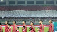 Suporter Indonesia membentangkan bendera raksasa saat laga Timnas Indonesia U-23 melawan Bahrain pada laga PSSI Anniversary Cu 2018 di Stadion Pakansari, Bogor, (26/4/2018). Bahrain unggul sementara 1-0. (Bola.com/Nick Hanoatubun)