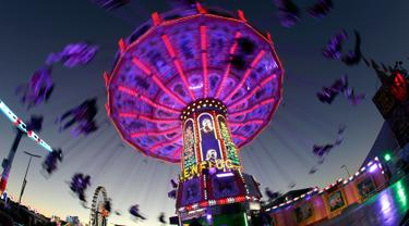 Pengunjung menikmati wahana ayunan ontang-anting saat berlangsungnya festival bir Oktoberfest di Munich, 27 September 2018. Oktoberfest adalah rangkaian festival terbesar di dunia yang diadakan setiap tahun oleh masyarakat Jerman. (AP/Matthias Schrader)