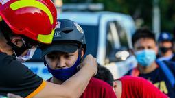 Seorang anggota lembaga swadaya masyarakat membagikan helm dan selempang reflektif secara gratis kepada pengendara sepeda di Manila, Filipina (9/7/2020). (Xinhua/Rouelle Umali)