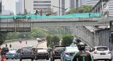 Suasana lalu lintas saat pekerja membongkar jembatan penyeberangan orang (JPO) Tosari, Jakarta, Minggu (16/12). Pembongkaran JPO Tosari ditergetkan selesai pada 20 Desember 2018. (Merdeka.com/Iqbal Nugroho)