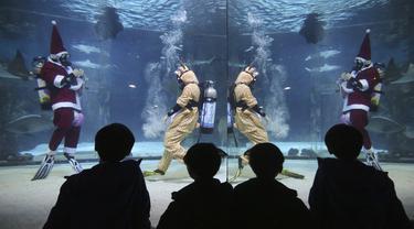 Sejumlah pengunjung menyaksikan aksi penyelam mengenakan pakaian Sinterklas di Coex Aquarium, Seoul, Korea Selatan (4/12/2019). Kegiatan ini untuk menyambut Natal 2019. (AP Photo/Ahn Young-joon)