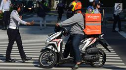 Petugas Dishub menegur pengendara motor yang berhenti di marka jalan saat Polda Metro Jaya mensosialisasikan terkait penambahan kamera untuk mendukung penerapan sistem Electronic Traffic Law Enforcement (E-TLE) atau tilang elektronik di Jalan Thamrin, Jakarta, Kamis (25/4). (merdeka.com/Imam Buhori)
