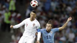 Duel pemain Portugal, Cristiano Ronaldo (kiri) dan pemain Uruguay, Diego Laxalt pada laga 16 besar Piala Dunia 2018 di Fisht Stadium, Sochi, Rusia, (30/6/2018). Portugal kalah 1-2. (AP/Andrew Medichini)