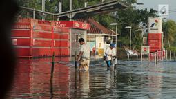 Dua orang pria melintasi area SPBU yang terendam banjir rob akibat naiknya permukaan air laut di Muara Baru, Penjaringan, Jakarta Utara, Kamis (7/12). Banjir rob juga merendam ratusan rumah warga di Muara Baru dan Luar Batang. (Liputan6.com/Johan Tallo)