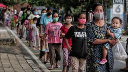Warga menerapkan jaga jarak aman saat antre untuk mendapatkan takjil di Jalan Cempaka Putih Raya, Jakarta, Senin (11/5/2020). Setiap hari selama Ramadan, masyarakat sekitar membagikan 350 takjil kepada warga kurang mampu dan terdampak virus corona COVID-19. (Liputan6.com/Johan Tallo)