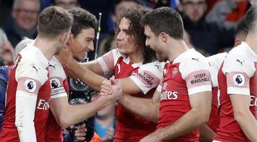 Para pemain Arsenal merayakan gol yang dicetak oleh Laurent Koscielny ke gawang Chelsea pada laga Premier League di Stadion Emirates, Sabtu (19/1). Arsenal menang 2-0 atas Chelsea. (AP/Frank Augstein)