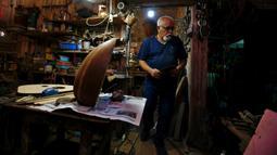 Mahmoud Abdulnabi membuat oud di bengkelnya di Baghdad, Irak, Kamis (17/6/2021). Setelah bertahun-tahun terpuruk karena takut akan serangan ISIS, para pembuat oud mengatakan kerajinan tradisional mereka kembali berkembang di Irak sejak kelompok ekstremis dikalahkan. (AP Photo/Hadi Mizban)