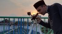 Seorang pengurus sedang mengami hilal dengan alat bantu teropong di Observatorium Assalam, Kamis (23/4).(Liputan6.com/Fajar Abrori)