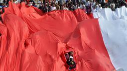 Bendera raksasa yang sengaja dibawa untuk mengiringi Kirab Budaya terlihat robek bagian tengahnya sehingga warga yang membawanya terlihat, Jakarta, Senin (20/10/2014) (Liputan6.com/Miftahul Hayat)