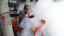 Warga memegang hidung dan radio portabelnya saat mencoba menghindari disinfeksi di desanya sebagai pencegahan penyebaran COVID-19 di Manila, Filipina, Senin (15/3/2021). Lonjakan kasus COVID-19 di Filipina menambah kekhawatiran atas lambannya vaksinasi dan keengganan publik. (AP Photo/Aaron Favila)