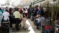 Penumpang yang terdampar menunggu penerbangan mereka setelah aksi mogok kerja di bandara JKIA, Nairobi, Rabu (6/3). Petugas pemadam meninggalkan landasan pacu, pegawai keamanan, staf check in, dan staf bagasi juga berhenti bekerja (AP Photo/Khalil Senosi)