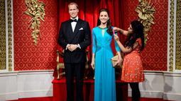 Seorang pekerja Madame Tussauds tampak merapikan penampilan baru patung lilin Pangeran Williams dan Kate Middleton, London, Rabu (2/7/14). (AFP PHOTO/Leon Neal)