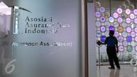 Pekerja tengah membersihkan logo anggota asuransi jiwa dipajang di kantor Asosiasi Asuransi Jiwa Indonesia (AAJI) Jakarta, Selasa (23/8). Jumlah tersebut tercatat naik sebesar 13,7% dibandingkan pada 2015. (Liputan6.com/Angga Yunair)