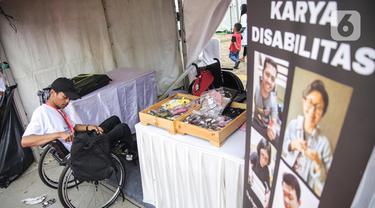 Penyandang disabilitas menjaga booth pada acara puncak peringatan Hari Disabilitas Internasional 2019 di Plaza Barat Gelora Bung Karno, Jakarta, Selasa (3/12/2019). Acara ini mengangkat tema 'Indonesia Inklusi, Disabilitas Unggul'. (Liputan6.com/Faizal Fanani)