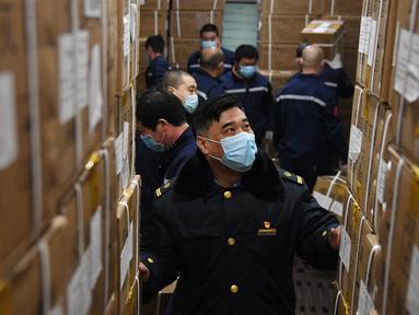 Para staf memeriksa sejumlah baju pelindung yang dimuat di Stasiun Kereta Barat Beijing di Beijing, ibu kota China (4/3/2020). Total 20.000 baju pelindung disalurkan ke Wuhan guna membantu upaya kota itu memerangi wabah coronavirus baru. (Xinhua/Zhang Chenlin)