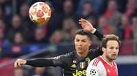 Megabintang Juventus, Cristiano Ronaldo berebut bola dengan bek Ajax Amsterdam, Daley Blind pada laga pertama perempat final Liga Champions 2018-2019 di Amsterdam Arena, Rabu (10/4). Juventus harus puas bermain imbang 1-1 di kandang Ajax Amsterdam. (EMMANUEL DUNAND / AFP)