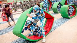 Sejumlah anak-anak melakukan simulasi latihan militer di sebuah taman kanak-kanak di provinsi Henan, China (30/5). Latihan militer ini dilakukan untuk menjelang Hari Anak Internasional yang jatuh pada 1 Juni. (AFP)