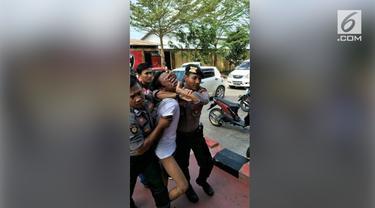 Seorang pria sambil membawa ransel menerobos pagar Polresta Samarinda, Sabtu (2/6).