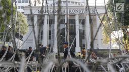 Personel Brimob melintas di depan Gedung Mahkamah Konstitusi (MK), Jakarta, Selasa (25/6/2019). Jelang sidang pembacaan putusan akan digelar pada Kamis (27/6), sekitar 47.000 personel keamanan gabungan akan disiagakan di Ibu Kota DKI Jakarta. (Liputan6.com/Helmi Fithriansyah)