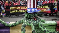 Gerakan Buruh untuk Rakyat (Gebrak) berunjuk rasa di depan Kedubes Amerika Serikat, Jakarta, Selasa (12/2). Massa pendemo membawa serta boneka gurita raksasa warna hijau yang dikenakan topi bermotif bendera Amerika Serikat. (Liputan6.com/Faizal Fanani)
