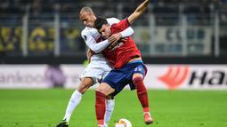 Duel antara Andrija Pavlovic dan Miranda pada leg 2, babak 16 besar Liga Europa yang berlangsung di stadion Giuseppe Meazza, Milan, Jumat (22/2). Inter Milan menang 4-0 atas rapid Wien. (AFP/Miguel Medina)