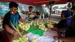 Pedagang melayani pembeli kulit ketupat di bawah kolong jembatan kawasan Pesanggrahan, Jakarta, Senin (10/5/2021). H-3 menjelang Hari Raya Idul Fitri 1442 H, penjualan kulit ketupat mulai marak yang dijual dengan harga Rp 8.000 per 10 buahnya. (Liputan6.com/Johan Tallo)