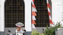 Seorang wanita memegang bunga di sekitaran Jalan Kali Besar Barat kawasan Kota Tua, Jakarta, Minggu (19/9/2021). Meski Jakarta masih dalam masa PPKM level 3, kawasan ini mulai ramai dikunjungi warga untuk berwisata atau sekedar berfoto. (Liputan6.com/Helmi Fithriansyah)