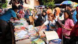 Warga memilih buku tulis yang dijajakan pedagang di sekitar Pasar Asemka, Jakarta, Rabu (5/7). Jelang bergantinya tahun ajaran baru, sejumlah warga berburu peralatan sekolah di kawasan Pasar Asemka Jakarta. (Liputan6.com/Helmi Fithriansyah)