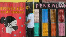 Warga membuat mural Lawan Virus Corona di Lapangan Bulutangkis, Kampung Kali Pasir, Jakarta, Selasa (7/4/2020). Mural dengan swadaya sendiri mengajak warga untuk memutus rantai penyebaran Corona Covid-19 dengan diam di rumah dan tidak berkerumum di luar. (Liputan6.com/Fery Pradolo)