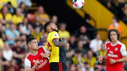 Andre Gray dari Watford berebut bola dengan kapten Arsenal, Granit Xhaka pada pekan kelima Liga Inggris 2019-2020 di Vicarage Road, Minggu (15/9/2019). Sempat unggul dua gol, Arsenal harus rela imbang 2-2 saat berjumpa tim tuan rumah Watford. (AP/Alastair Grant)