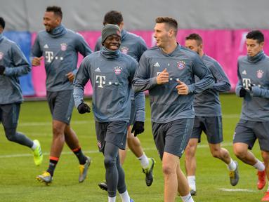 Para pemain Bayern Munchen melakukan pemanasan selama sesi latihan di Munich, Jerman selatan (12/3). Bayern Munchen akan bertanding melawan wakil Inggris, Liverpool pada leg kedua babak 16 besar Liga Champions. (AFP Photo/Matthias Balk)