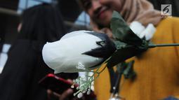 Seorang wanita menunjukkan mawar putih saat menyambut kedatangan penyidik senior KPK, Novel Baswedan di gedung KPK, Jakarta, Jumat (27/7). Novel absen 16 bulan lantaran berobat matanya setelah diserang air keras. (Merdeka.com/Dwi Narwoko)