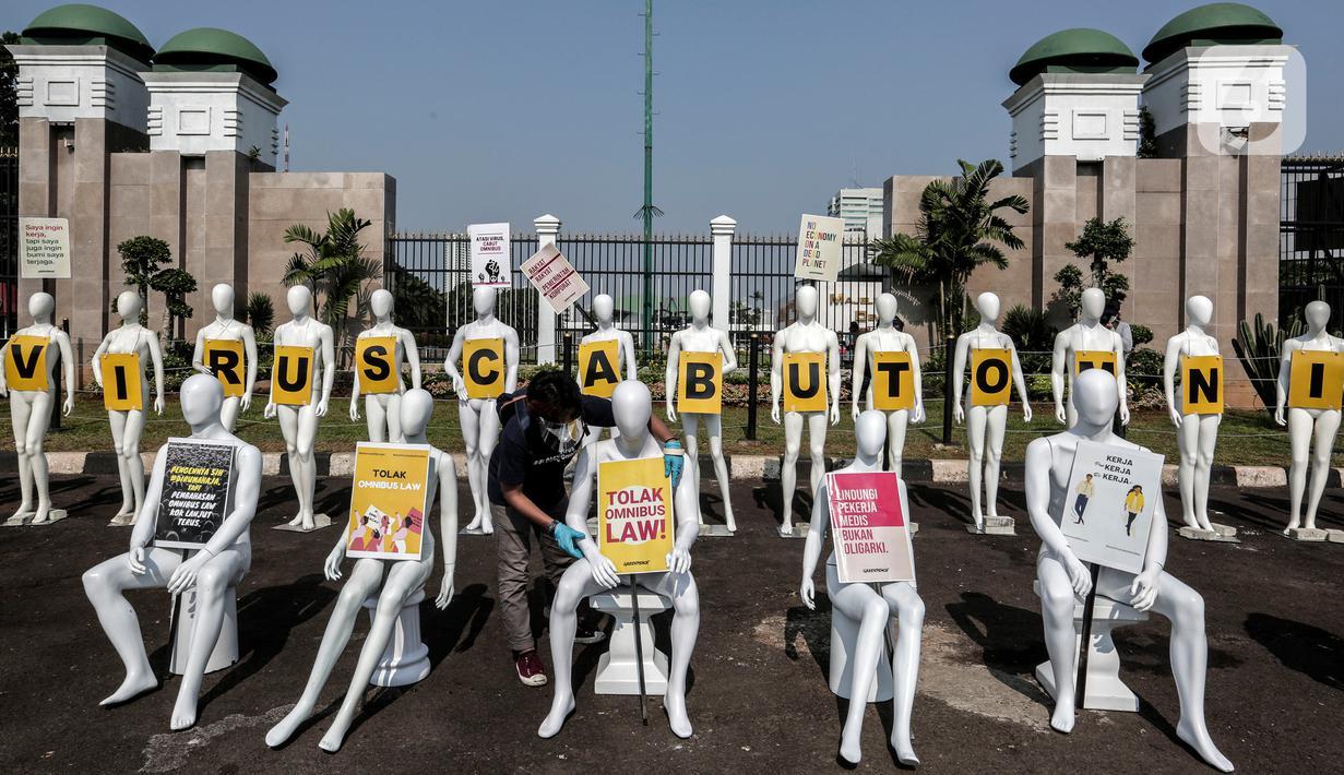 Aktivis Greenpeace Indonesia menata puluhan maneken saat menggelar aksi damai di depan gerbang kompleks DPR, Jakarta Pusat, Senin (29/6/2020). Aksi tersebut dilakukan sebagai bentuk penolakan terhadap RUU Omnibus Law. (Liputan6.com/Johan Tallo)
