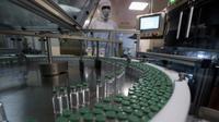 Seorang karyawan mengoperasikan mesin pengisi vaksin COVID-19 di Serum Institute of India, Pune, India, Kamis (21/1/2021). Serum Institute of India adalah pembuat vaksin terbesar di dunia dan telah dikontrak untuk memproduksi miliar dosis vaksin AstraZeneca-Oxford University (AP Photo/Rafiq Maqbool)