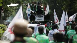 Massa pengemudi ojek online menaiki mobil komando sambil berorasi saat unjuk rasa menuju Istana Negara, Jakarta, Senin (15/5). Aksi tersebut menuntut adanya perbaikan pemberlakuan tarif dasar yang dirasa merugikan pengemudi. (Liputan6.com/Faizal Fanani)