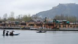 Seorang awak perahu Kashmir mengangkut penumpang saat hujan di Danau Dal di Srinagar (20/3). Danau Dal yang luas dan bening. Diatasnya terhampar gerombolan daun bunga lotus. (AFP Photo/Tauseef Mustafa)