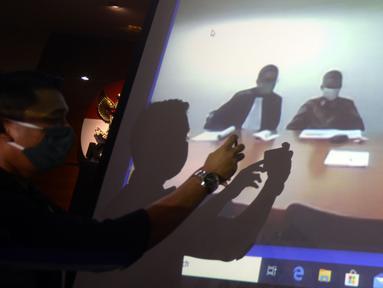 Mantan Komisioner KPU Wahyu Setiawan (tengah) mendengarkan Jaksa Penutut Umum membacakan dakwaan saat sidang secara daring di Gedung KPK, Jakarta, Kamis (28/5/2020). Wahyu menjalani sidang dakwaan terkait kasus dugaan menerima suap pengurusan PAW anggota DPR dari PDIP. (merdeka.com/Dwi Narwoko)
