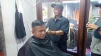 Abah Atrox tengah mempraktekan potongan rambut (Liputan6.com/Jayadi Supriadin)