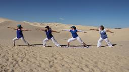 Peserta menghadiri kelas yoga yang diselenggarakan oleh komunitas YSYoga System di gurun Samalayuca, negara bagian Chihuahua, Meksiko pada 25 Mei 2019. Ratusan penggemar yoga mengikuti latihan bersama di bawah terik matahari dan beralaskan pasir. (Herika MARTINEZ/AFP)
