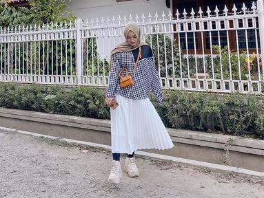 Putri Delina Andriyani, memang kerap membagikan outifit yang ia pakai di media sosialnya. Salah satunya saat ia memakai kemeja over-size yang dipadukan dengan rok panjang berwarna putih. Tas selmpang warna coklat menjadi tambahan penampilanny yang catchy.(Liputan6.com/IG/@putridelinaa)