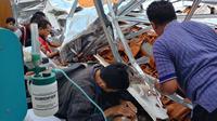 Seorang anak lindungi bapaknya saat atap RSAL Surabaya ambruk. Foto: (Dian Kurniawan/istimewa)